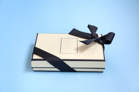 Gift box with colored ribbon as a gift for Christmas, New Year, Mothers Day, anniversary, birthday, party, isolated on a blue background, top view. Gift to a colleague at work