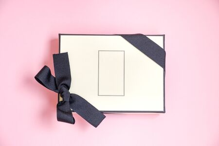 Gift box with colored ribbon as a gift for Christmas, New Year, Mothers Day, anniversary, birthday, party, isolated on a pink background, top view. Gift to a colleague at work