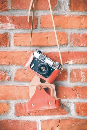 Vintage analog film camera with lens on a brick wall background.