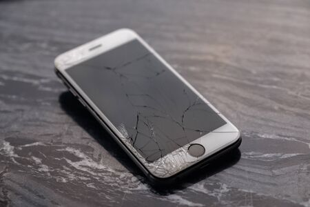 Broken and cracked smartphone screen. A broken smartphone lies on the table before repairing and replacing the monitor. Broken matrix.