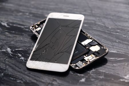 Broken and cracked smartphone screen. A broken smartphone lies on the table before repairing and replacing the monitor. Broken matrix. Close-up.