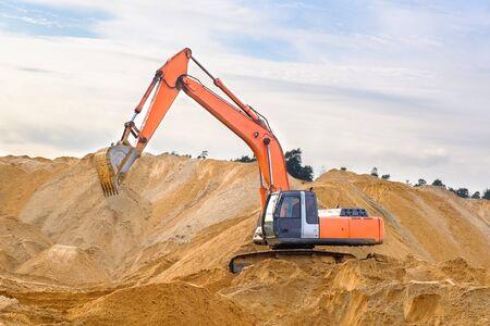Raupenbagger arbeitet auf einer Baustelle. Schwere Baumaschinen auf einem Hintergrund von Sandbergen. Eine Maschine tropft Sand mit einem Eimer.