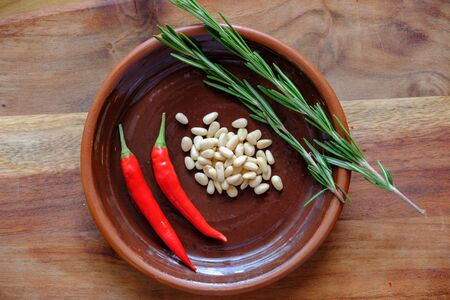 Fresh rosemary, hot red pepper and pine nuts on a clay plate on a wooden background with crystals of coarse white salt. The concept of a delicious and healthy diet.