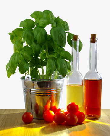 Foliate basil in metal bucket with fresh tomatoes and olive bottle on table, sunny backlight Stock Photo
