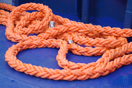 The reel of orange rope on dark blue paint background. Ship equipment.