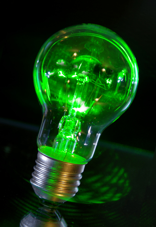Concept of classic bulb green power light with laser rays.