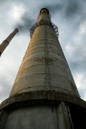 Old concrete high chimneys with black smoke. Ecology and global warming concept.
