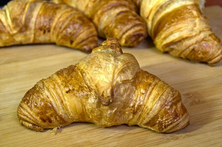 Fresh croissants on wooden board. Appetizing backed cake for breakfast. Stock Photo