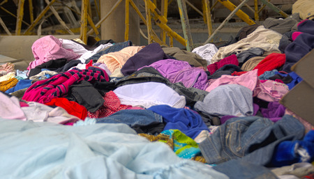 Abandoned heap of old worn clothes. Scattered colorful fabric. Stock Photo