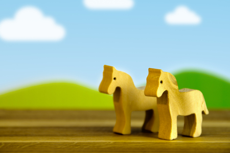 Eco wooden horses on cartoon landscape background. Silhouette of a toys cuted from wood.