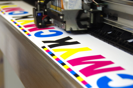 Plotter head printing CMYK test on white paper. Large digital inkjet machine work.
