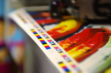 Inkjet plotter printing CMYK mark on white paper. Large digital printer machine.
