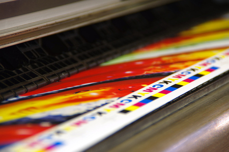 CMYK mark printed by inkjet plotter on white paper. Large digital printer machine. Foto de archivo
