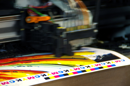 Inkjet printer plotter head moving over CMYK mark on white paper. Large digital printing machine. Archivio Fotografico