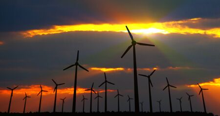 Wind turbines silhouette on dramatic sky background. Energy windmills in concept of ecological electric power.