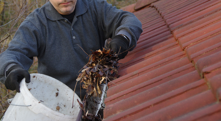 Man cleaning dirty gutter from moss and leaves. Building with unclean tile roof after winter. Spring cleaning. Stock Photo