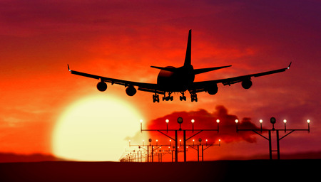 Airplane silhouette of Jumbo Jet lands at the airport during sunset. Shape of airplane and flashing runway lights.