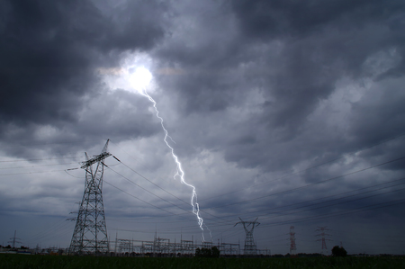 Lightning storm on electric tower. Dramatic sky and thunderstorm over energy station.