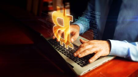 Man in a tie is typing on laptop with bitcoin hologram screen over keyboard. Cryptocurrency mining, blockchain, virtual money and futuristic economy concept. Natural hand camera shake. Banco de Imagens