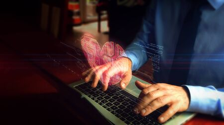 Man typing on laptop with cybernetic heart hologram screen over keyboard. Love, cyber dating, romantic, health and cardiology futuristic concept. Natural hand camera shake. Banco de Imagens