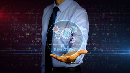 Man with dynamic data management symbols hologram on hand. Businessman and futuristic concept of Files storage, cyber security, computer using and digital protection technology with glitch effect.