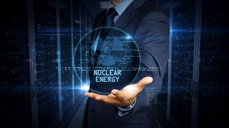 A businessman in a suit touch screen with nuclear energy symbol hologram. Man using hand on virtual display interface. Science, danger icon and cyber war futuristic concept.