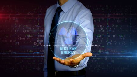 Man with dynamic nuclear energy symbol hologram on hand. Businessman and futuristic concept of science, danger icon and warning with light and glitch effect.