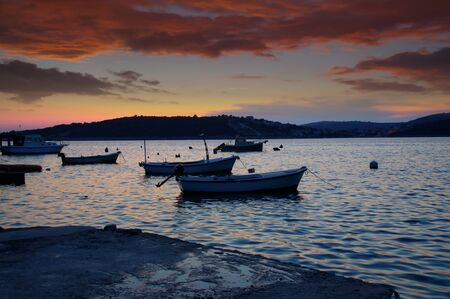 Seaport after sunset. Motor boats on the roadstead in a seaside bay. Dramatic sky and clouds in the background. Stok Fotoğraf - 129960604