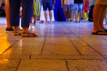 Crowds of tourists visiting the historic city. A trampled destination. Old cobble street at night.