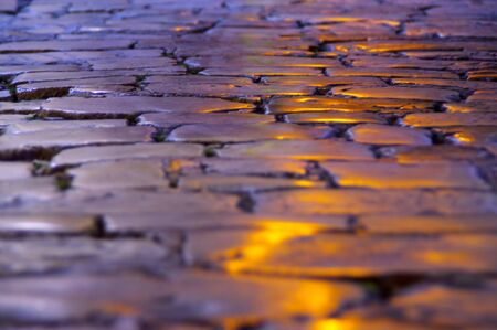 Yellow light on pavement street at night. Ancient stone footpath.