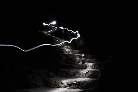 Light line on stone stairs. Abstract dark night scene.
