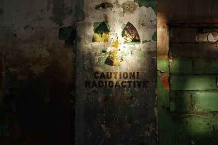 Radioactive warning on old damaged wall. Destroyed and forgotten building after nuclear disaster. Radiation symbol alert. Stock fotó