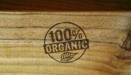 Organic 100 percent stamp printed on wooden box. Ecology, bio, gmo free, natural and healthy diet concept.
