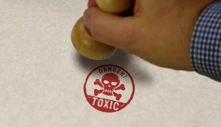 Toxic danger with skull stamp and stamping hand. Poison warning concept. Stock Photo