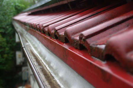 Wet tiles and gutter on the roof. Cover the house during the rain. Rainwater retention. Reklamní fotografie - 154387907