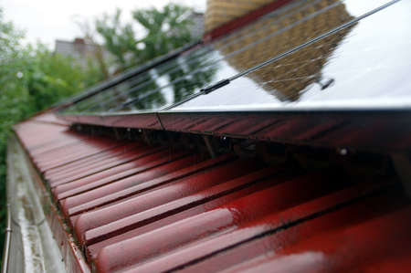 Wet solar panels on the roof tile. House photovoltaic energy in the rain.