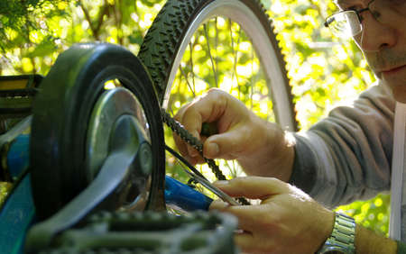 Taking care of the bike outdoors. Repair of the chain on a sprocket on a bicycle. Reklamní fotografie - 154916050