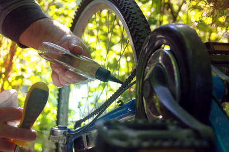 Taking care of the bike outdoors. Repair of the chain on a sprocket on a bicycle. Reklamní fotografie - 154917041