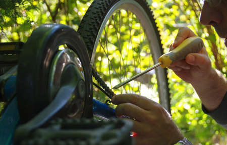 Taking care of the bike outdoors. Repair of the chain on a sprocket on a bicycle.