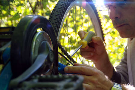 Taking care of the bike outdoors. Repair of the chain on a sprocket on a bicycle. Reklamní fotografie - 154916969