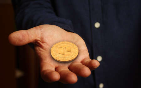 Neo altcoin cryptocurrency symbol golden coin in hand abstract concept. Reklamní fotografie