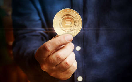 Solana altcoin cryptocurrency symbol golden coin in hand abstract concept.