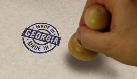 Made in Georgia stamp and stamping hand. Factory, manufacturing and production country concept.