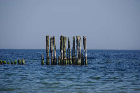 Old wooden breakwater by the sea. Rusty coastal protection.