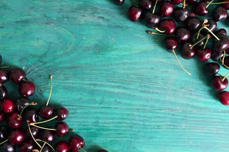 Fresh cherries on a green wooden background. Background for your design.