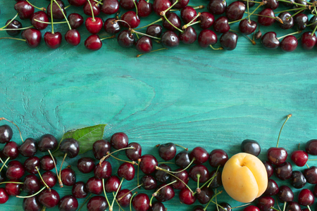 Fresh cherries on a wooden background. Background for your design.