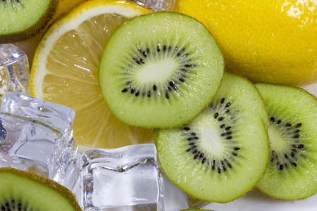 Kiwi fruit with ice and lemon slices in a bowl.