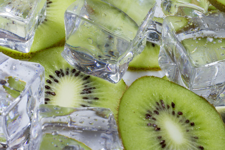 Kiwi fruit slices in a bowl with ice cubes. Stock Photo