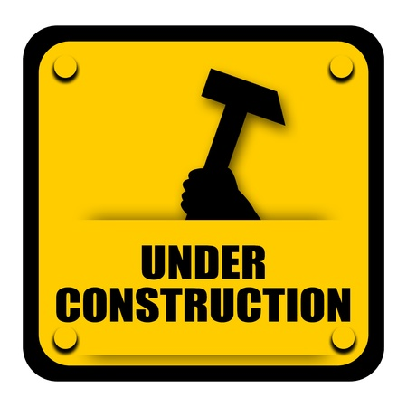 Under construction sign with hammer in the hand of worker isolated on white background photo