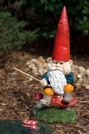 nain de jardin: Garden gnome de p�che sur un champignon et de la pens�e